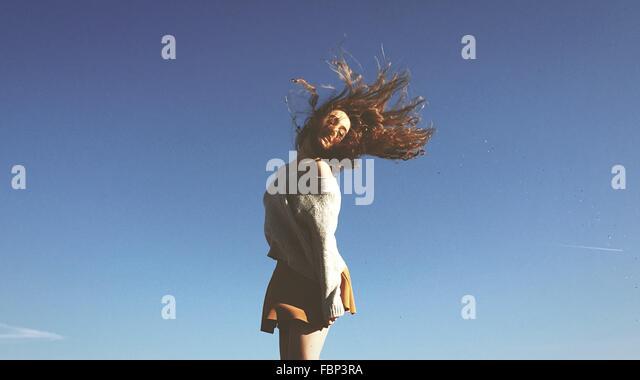 Junge Frau wirft Haar gegen blauen Himmel Stockbild