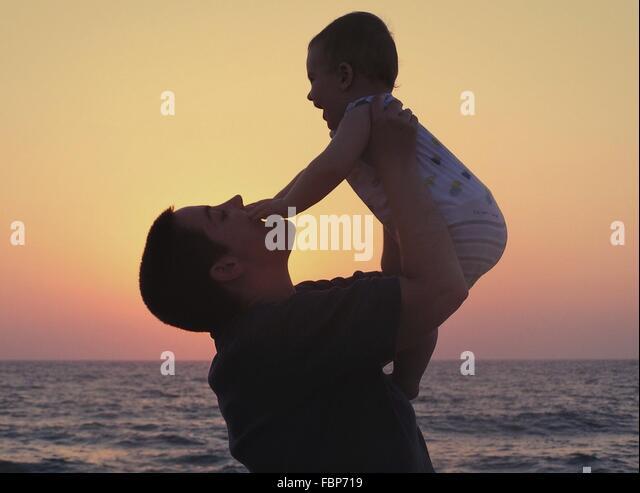 Mutter mit Kind am Strand spielen Stockbild