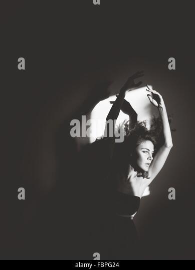 Porträt der jungen Frau mit erhobenen Armen Stockbild
