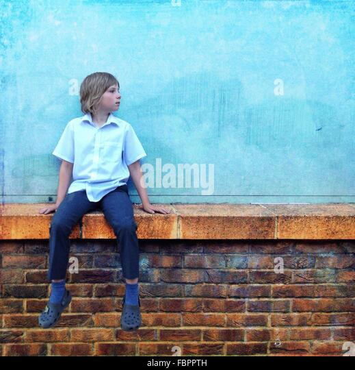 Teenager tragen blaues Hemd und Jeans sitzen auf Wand Stockbild
