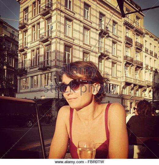 Lächelnde junge Frau in ein Café im freien gegen Gebäude Stockbild