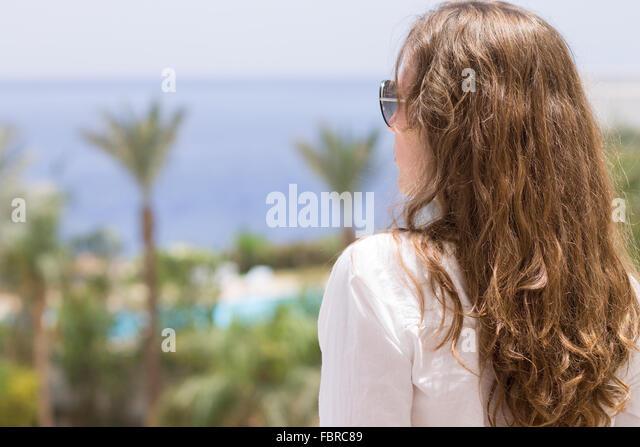 Junge Frau mit langen lockigen Haaren, Blick auf Meer. Sommer Urlaub Hotel Hintergrund mit Textfreiraum Stockbild