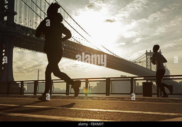 Sonnenaufgang über die Manhattan Bridge New York City morgen als zwei Jogger laufen North East River Esplanade Stockbild
