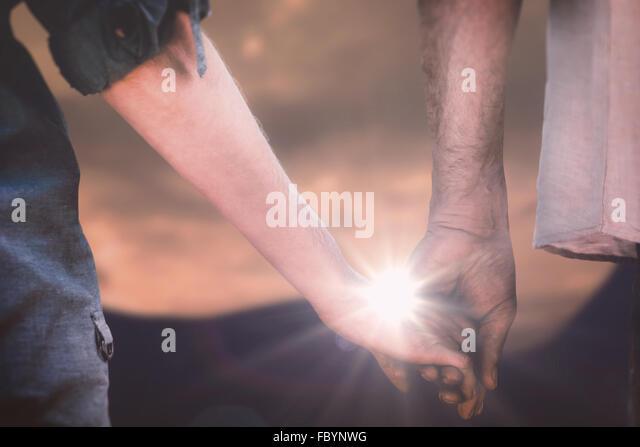 Zusammengesetztes Bild paar Holding Hände im park Stockbild