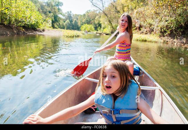 Mädchen Rudern Kanu flussabwärts Stockbild