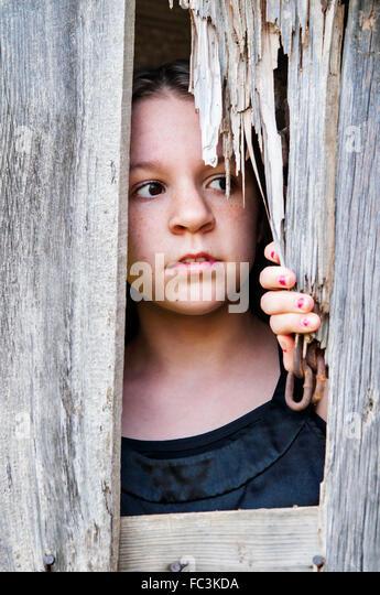 Mädchen auf der Suche aus der Scheune Stockbild