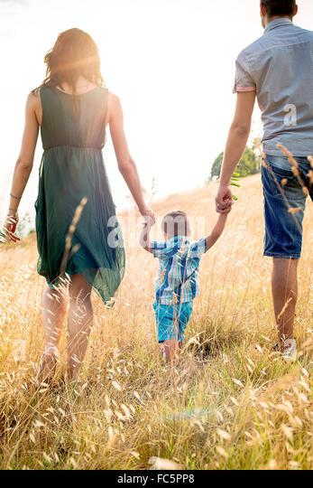 Eltern gehen mit jungen Sohn im Feld, Ansicht von hinten Stockbild