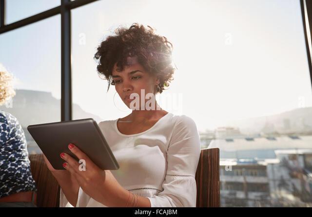 Porträt der jungen Frau fleißig an digital-Tablette an einem sonnigen Tag. Attraktive Afrikanerin Internetsurfen Stockbild