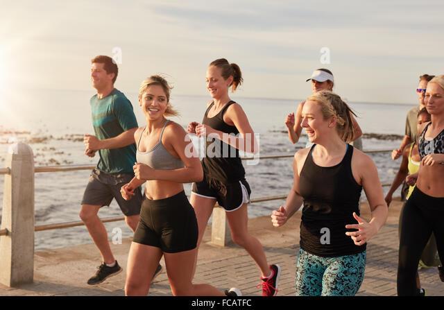 Porträt von gesunden jungen Männern und Frauen zusammen direkt an Strandpromenade laufen. Laufenden Club Stockbild