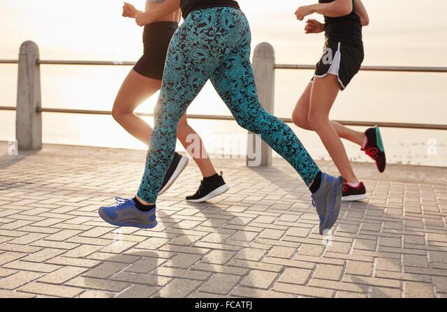 Bild von Jugendlichen, die entlang dem Meer abgeschnitten. Fitness-Gruppe laufenden Training gemeinsam im Freien Stockbild