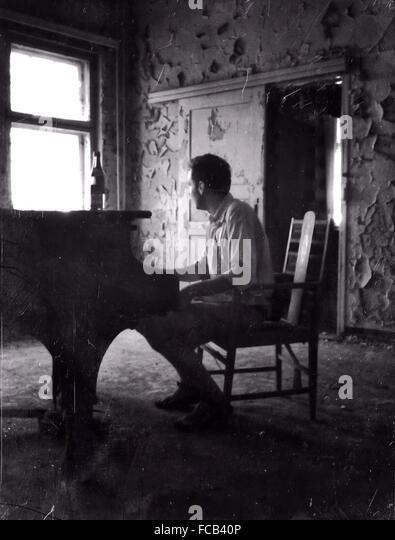Gesamte Länge der Pianist spielt Klavier im verlassenen Haus Stockbild