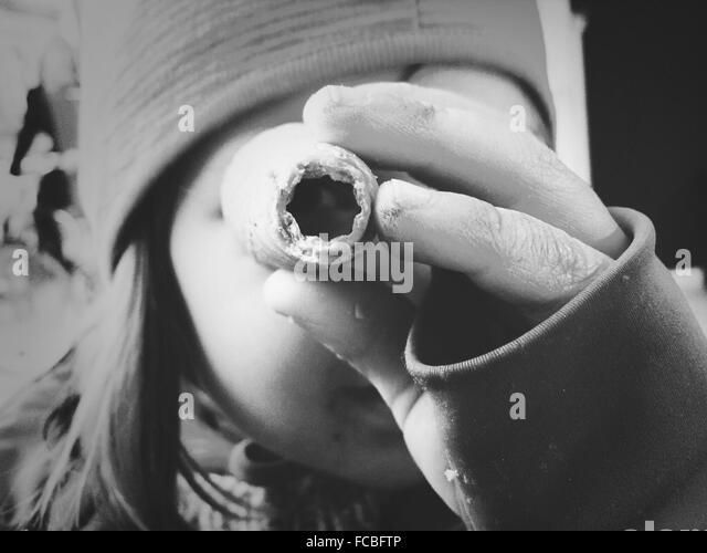 Close-up Portrait der Frau, die durch ein Objekt Stockbild