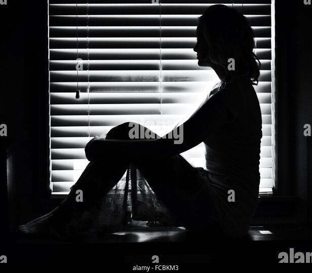 Frau sitzt gegen Fenstervorhänge zu Hause Stockbild
