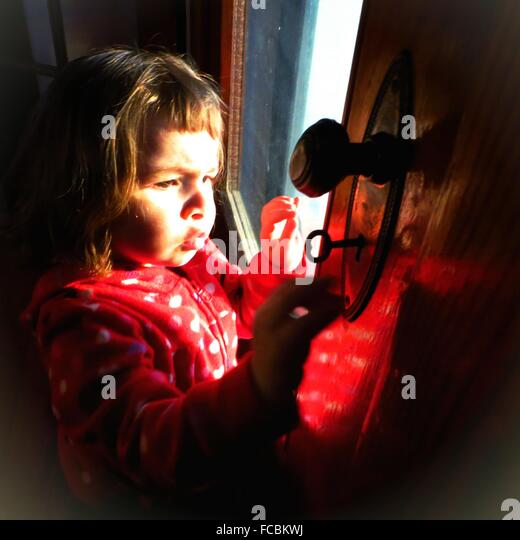 Niedliche Mädchen öffnende Tür mit Schlüssel zu Hause Stockbild