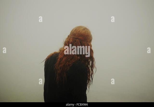 Rückansicht einer Frau mit langen roten Haaren Stockbild