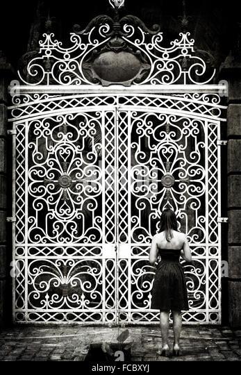 Rückansicht der Frau stand vor großen geschlossenen Toren Stockbild