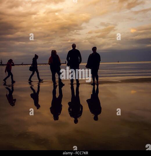Silhouette Menschen am Strand in der Abenddämmerung Stockbild