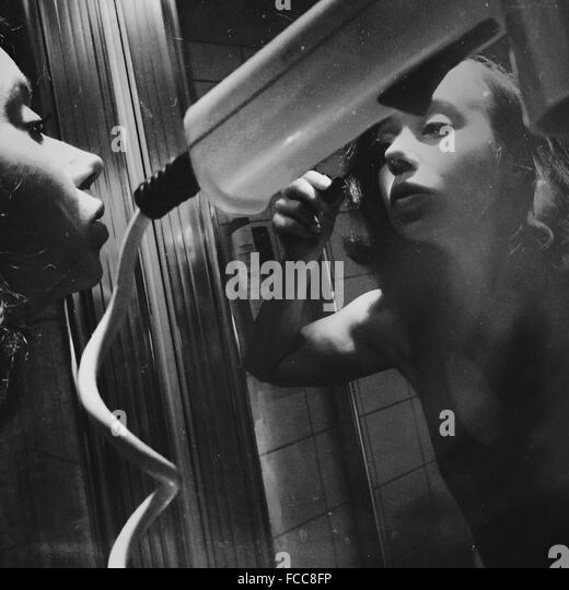 Junge Frau, die Anwendung von Mascara beim Spiegel betrachten Stockbild