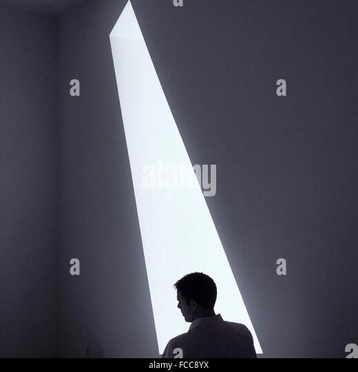 Rückansicht eines jungen Mannes wegschauen gegen Wand Stockbild