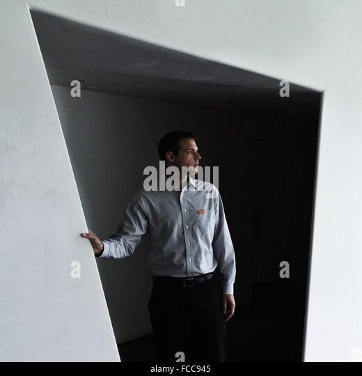 Junger Mann wegsehen gegen Wand Stockbild