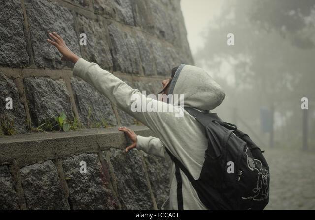 Teenager berühren Steinmauer Stockbild
