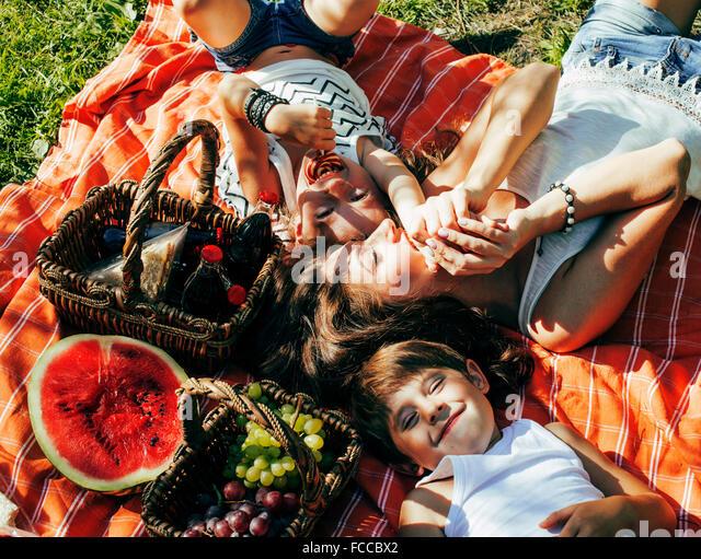 niedliche glückliche Familie Picknick auf grünen Rasen Mutter und Kinder, warmen Sommerferien schließen Stockbild