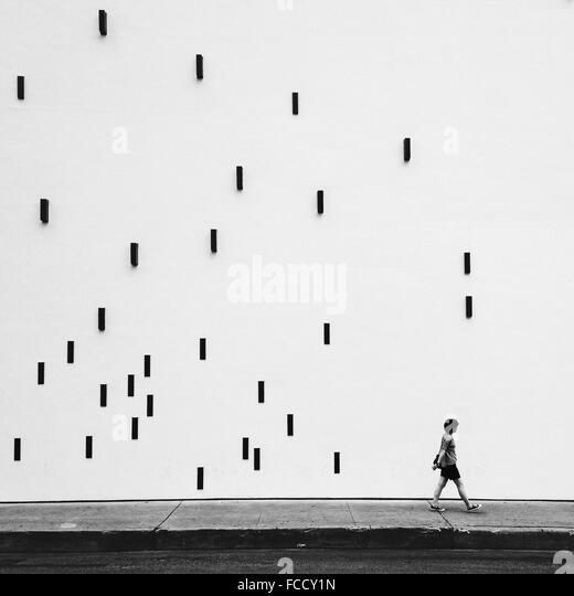 Mann zu Fuß auf Bürgersteig durch künstlerische Wand Stockbild