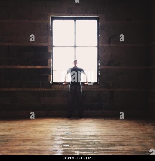 Mann an einem Fenster gelehnt Stockbild