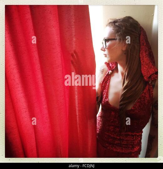 Junge Frau, die hinter dem roten Vorhang Stockbild