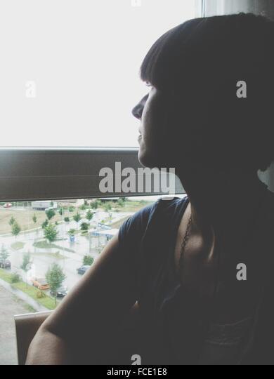 Frau, die durch Fenster Stockbild