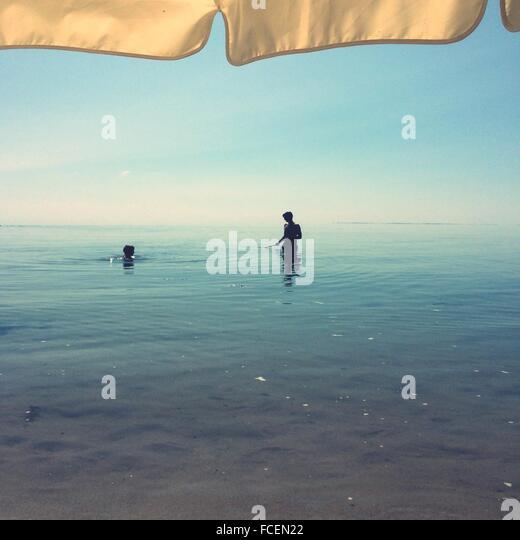 Vater und Sohn im Meer am Strand Stockbild