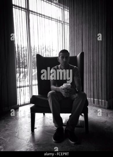 Porträt des jungen Mann mit Kaffee auf Ohrensessels zu Hause sitzen Stockbild
