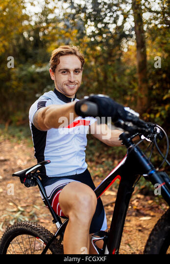 Porträt des Lächelns Mountainbiker im Wald Stockbild