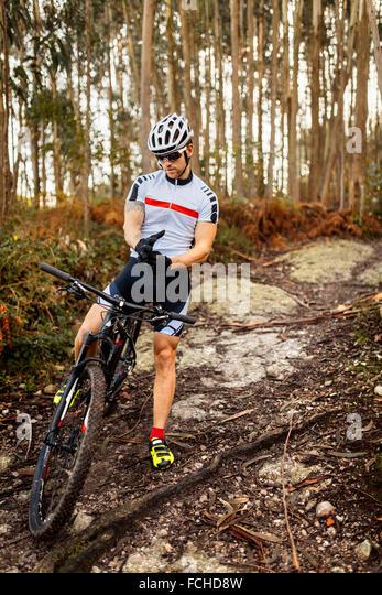 Mountainbiker im Wald sich erholend Stockbild