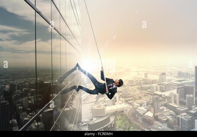 Konzept des Wettbewerbs mit dem Geschäftsmann Bürogebäude mit Seil klettern Stockbild