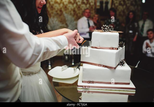 Braut und Bräutigam ist schneiden Kuchen Stockbild