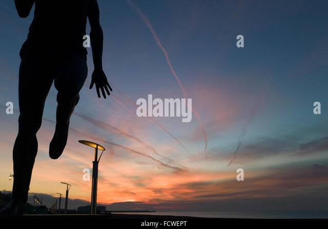 Silhouette der Statue von Steve Ovett, Runner, Brighton Seafront, bei Tagesanbruch, dramatische Sonnenaufgang Himmel Stockbild
