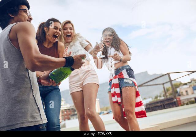 Junger Mann mit Freundinnen im Hintergrund Lachen und Spaß stehen eine Flasche Champagner zu öffnen. Junge Stockbild