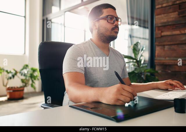 Porträt des jungen männlichen Foto-Editor bei der Arbeit in seinem Büro. Männliche Grafik-Designer Stockbild