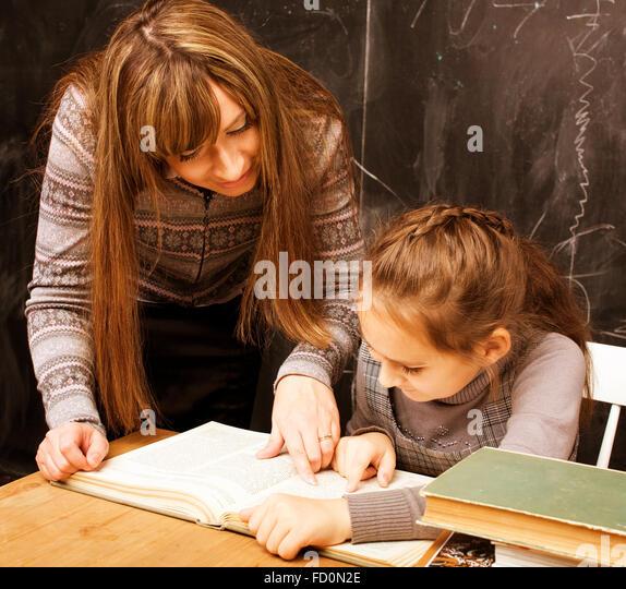 Lehrer mit Schüler im Klassenzimmer an Tafel schreiben Stockbild