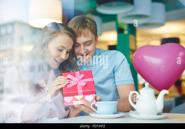 Junge überrascht Frau ihrem Freund Geschenk im Café öffnen Stockbild