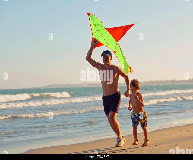 Vater mit Sohn, Sonnenuntergang an der Küste mit Drachen, glückliche Familie Stockbild