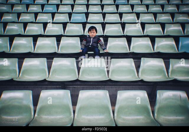 Junge sitzt auf Stuhl im Stadion Stockbild