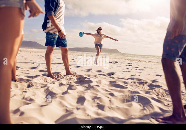 Niedrigen Winkel Aufnahme junge Frau läuft am Strand mit einem Ball mit ihren Freunden im Vordergrund stehen. Stockbild