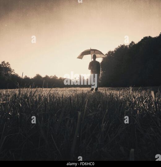 Mann, der im Feld mit Regenschirm gegen Himmel Stockbild