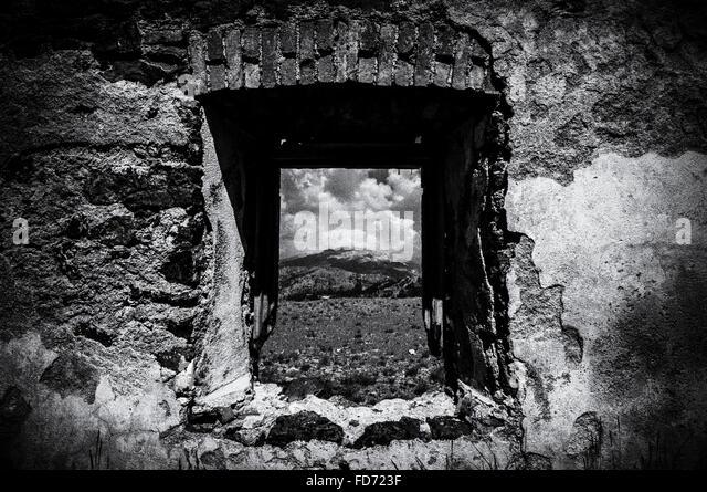 Berg durch verlassene Fenster gesehen Stockbild