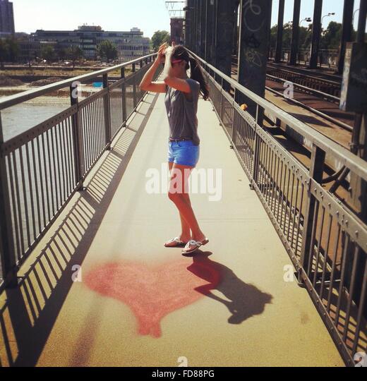 In voller Länge der jungen Frau auf Fußgänger Gehweg Brücke mit Herzen gestalten Malerei Stockbild