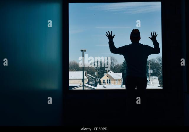 Rückansicht des Silhouette Mann am Fenster Stockbild