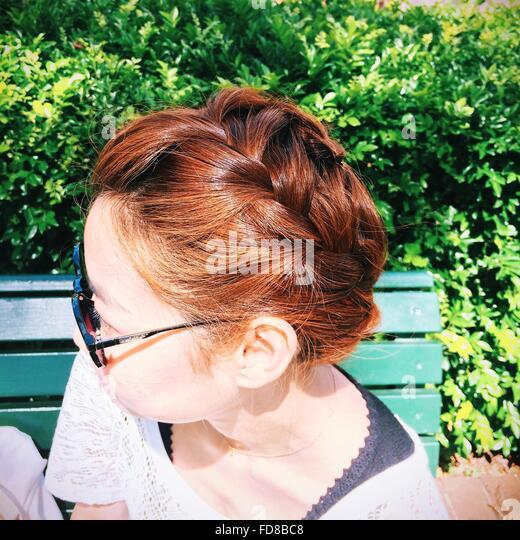 Seitenansicht der Frau mit geflochtenen Haaren, Sonnenbrille Stockbild