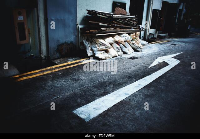 Pfeilmarkierung auf der Straße zeigt auf Stapel von Säcken Stockbild